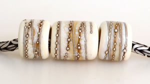 Ivory Silver Wraps Euro Charms Size: 10x12 & 15x12 mm Amount: 3 Beads Hole Size: 5 mm Three dark ivory glossy tube beads decorated with fine silver.  Default Title
