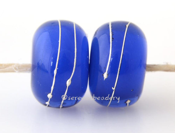 Dark Blue Thunder A layer of blue thunder over dark blue with a silver wrap.   6x12 mm with a 2.5 mm hole. Price is per bead. Glossy,Matte