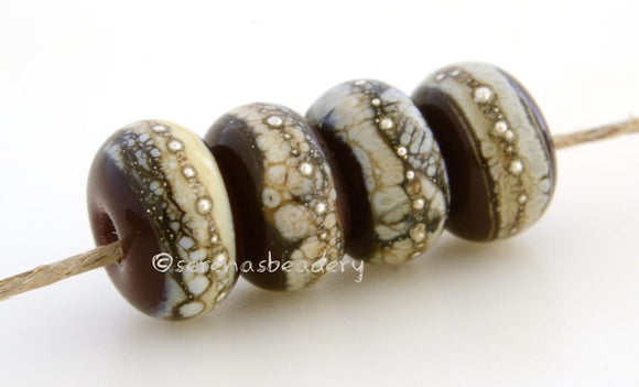 Dark Brown Granite with Fine Silver Dark brown wrapped in silvered ivory and fine silver droplets. 5x11 mm 2.5 mm hole Price is per bead with discounts for larger quantities. Glossy,Matte