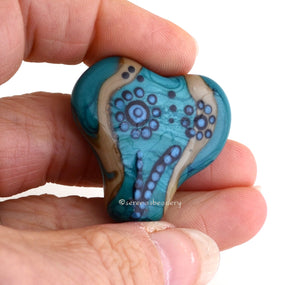 Hearts and Flowers Festive flowers on a mildly-heart shaped focal bead in turquoise, dark sand, black and teal. 30 mm from hole to hole 35 mm at widest point Default Title