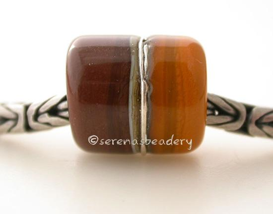 Chocolate Butternut European Charm with Fine Silver One European charm style bracelet bead with chocolate brown and butternut yellow, silvered ivory, and fine silver. Bead Size: approximately 14x12 mm Amount: 1 Bead Hole Size: 5 mm Glossy,Matte