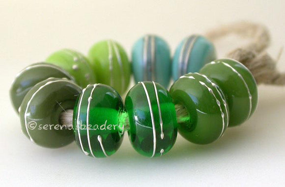 Fine Silver Greens A set of green colored lampwork beads with 5 different pairs. From top left going counter-clockwise - copper green, pea green, olive, emerald, and mystic green. Each silver wrap is carefully burnished onto the glass bead while it is still hot. Bead Size: 6x11 mm Amount: 10 Beads Hole Size: 2.5 mm Also available in a 7x14 mm size for .00 extra. Glossy,6x11mm,Glossy,7x14mm,Matte,6x11mm,Matte,7x14mm