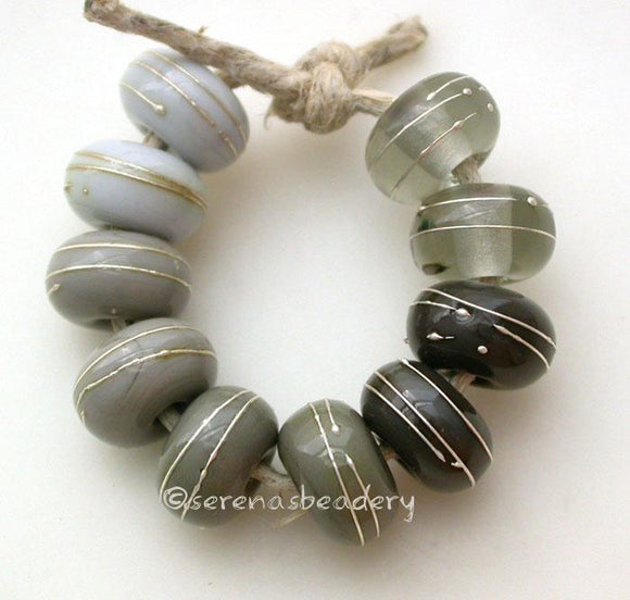 Fine Silver Grays A set of grey colored lampwork beads with 5 different pairs. From top left going counter-clockwise - pearl gray, light gray, dark gray, adamantium, and transparent gray. Each silver wrap is carefully burnished onto the glass bead while it is still hot. Bead Size: 6x11 mm Amount: 10 Beads Hole Size: 2.5 mm Also available in a 7x14 mm size for .00 extra. Glossy,6x11mm,Glossy,7x14mm,Matte,6x11mm,Matte,7x14mm