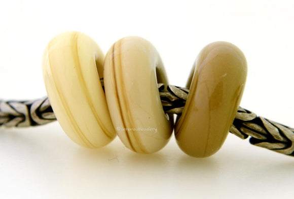 Boho Chic Trio Euro Charm Set A trio of European charm bracelet beads in ivory, sandstone, and sage.These lampwork beads will fit your European charm style bracelet.7x13-14 mm3 Beads5 mm holeprice is per bead set Glossy,Matte