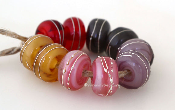 Mellow Mystics A set of mellow mystic lampwork beads with 5 different pairs - red, grey, violet, pink, and beige. Each silver wrap is carefully burnished onto the glass bead while it is still hot. Bead Size: 6x11 mm Amount: 10 Beads Hole Size: 2.5 mm Also available in a 7x14 mm size for .00 extra. Glossy,6x11mm,Glossy,7x14mm,Matte,6x11mm,Matte,7x14mm