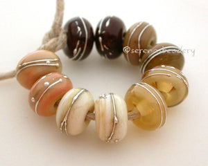 Neutrals With Fine Silver A set of neutral colored lampwork beads with 5 different pairs. From top left going counter-clockwise - brown, avocado, mystic beige, ivory, and stone ground.Each silver wrap is carefully burnished onto the glass bead while it is still hot.Bead Size: 6x11 mmAmount: 10 BeadsHole Size: 2.5 mmAlso available in a 7x14 mm size for .00 extra. Glossy,6x11mm,Glossy,7x14mm,Matte,6x11mm,Matte,7x14mm