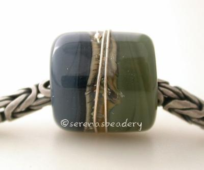 Olive Steel European Charm with Fine Silver One european charm style bracelet bead with olive green and steel blue, silvered ivory, and fine silver.Bead Size: approximately 12x11 mmAmount: 1 BeadHole Size: 5 mm Glossy,Matte