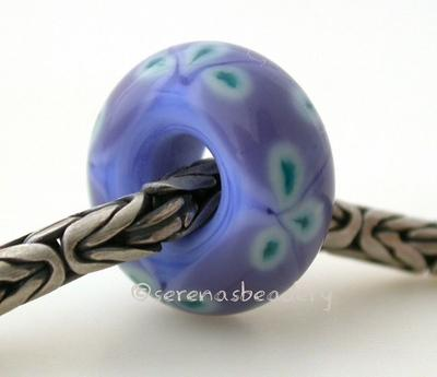 Periwinkle Lilac and Green Flower European Charm One periwinkle blue and lilac purple bead with copper green flowers and a hole large enough for a european charm bracelet. Will also fit your biaga or troll bracelet. Silver bracelet is not included.Bead Size:7x15 mmAmount:1 BeadHole Size:5 mm Glossy,Matte