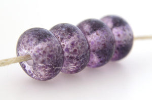 Royal Reflections Crystal clear lampwork glass beads with tiny bits of purple frit.Bead Size: 6x11-12 or 7x13-14 mmHole Size: 2.5 mmprice is for one bead with a discount for 4 or more 11-12 mm,Glossy,13-14 mm,Glossy,11-12 mm,Matte,13-14 mm,Matte