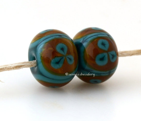 Teal Raku Round Flower Teal green and raku 3 petal flower pair. Size: 8x12 mm Amount: 2 Beads Hole Size: 1.5 mm   Glossy,Matte