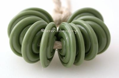 Olive Opaque Wavy Disk Spacer 10 wavy disks in olive green2 sizes available: 11-12 mm with 1.5 mm hole or 13-14 mm with 2.5 mm holeprice is per 10 disks 11-12 mm 1.5 mm hole,12-13 mm 2.5 mm hole