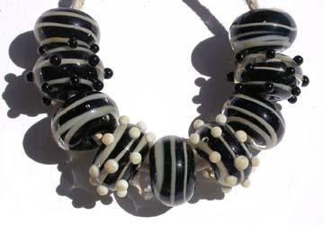 Black and Ivory Spiral 9 black beads encased with an ivory spiral stripe with some decorated either with black or ivory mini dotsapproximately 6x11 mm Default Title