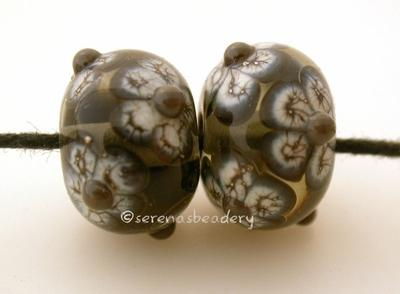 Gray Silvered Ivory Flowers a pair of transparent gray beads with black and silvered ivory flowers and adamantium centers6x12 mmmade on a 1/16, mandrelalso available with opaque grey Glossy,Matte