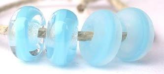 Dark Sky Blue Ribbon Color Notes: dark sky blue ribbon cased in clear 5x10 mm Donut- This is my basic spacer size. It is made on a 3/32 mandrel with a 2.5 mm hole. Other available sizes and shapes: 4x8 mm Round- A miniature sized spacer with a 1.5 mm hole. Lentil- 12x13 mm in size with a 1.5mm hole. Pillow- 14 mm square with a 1.5 mm hole. Disk- 3x13 mm with a 2.5 mm hole. Also 6x12 mm donut- A larger donut with a 2.5 mm hole. 8x15 mm Super Sized- A humungous spacer with a 3.5 mm hole. It is perfect for str