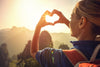 woman-wearing-backpack-makes-heart-hands-symbol-in-front-of-mountain-range