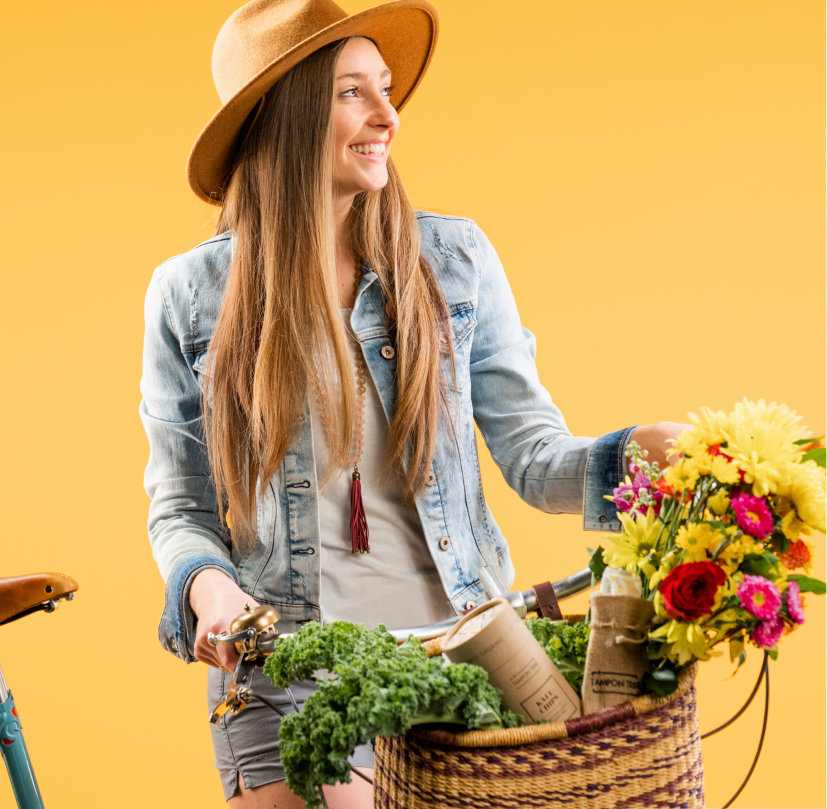 Smiling casual woman in straw hat with a wicker basket filled with kale, flowers, and other organic goods.