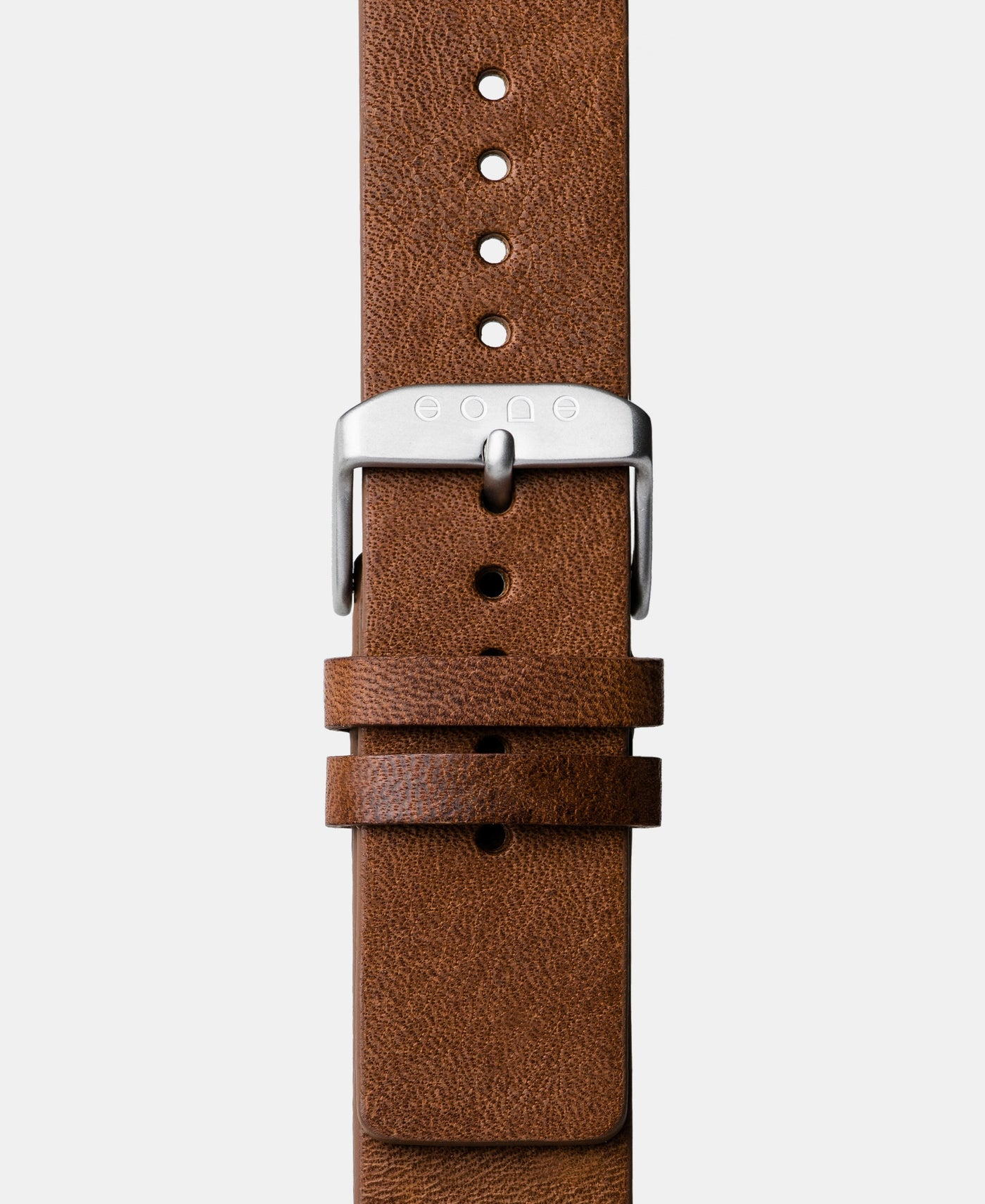 A photo shows the strap lying on a flat surface. One part has a buckle and the other part has a series of holes for an adjustable fit.