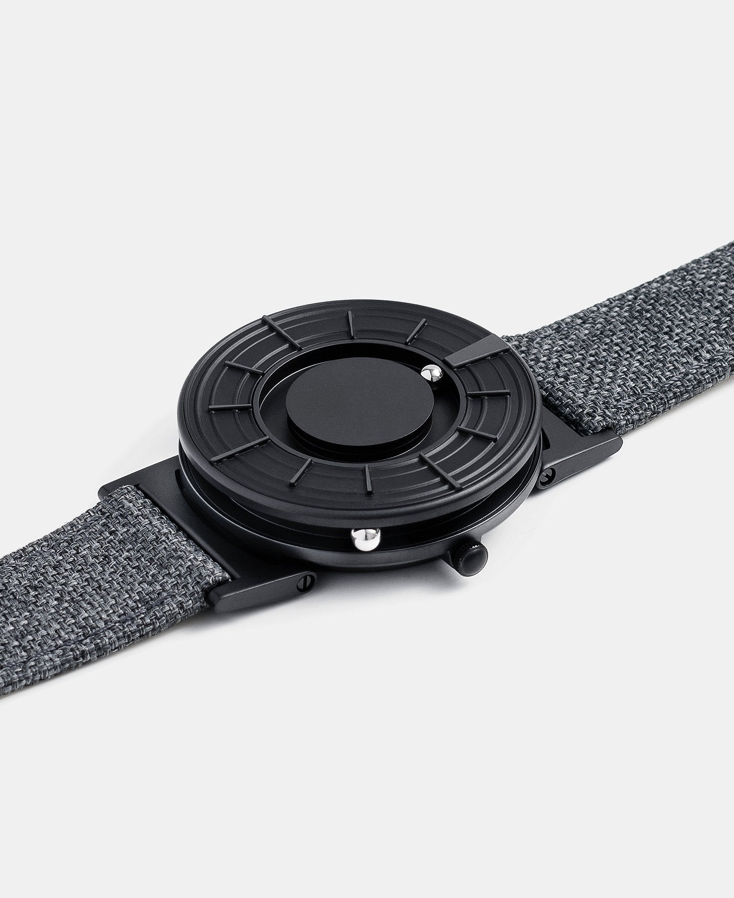 Load image into Gallery viewer, A photo of the watch lying flat on a surface. The recessed track around the outside of the watch face is shown with the hour ball bearing in the track. The raised markers are noticeable from this perspective.