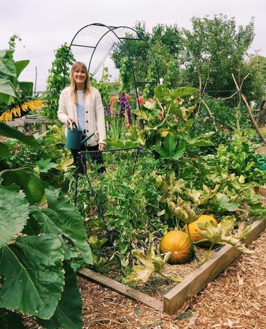 Emma in allotment, with squashes in a raised bed