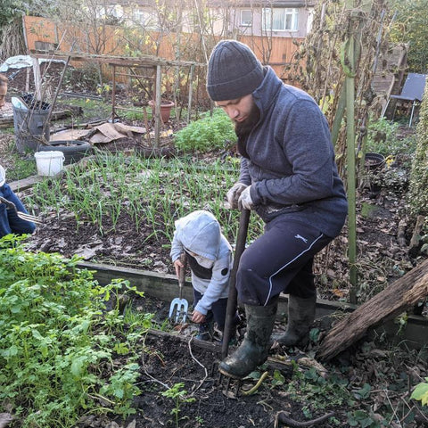 Mothin with his child, digging a raised bed in the garden