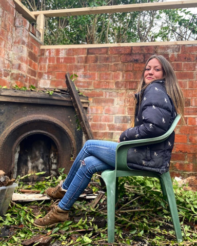 Danni sitting by a Victorian shed, with foliage around her feet