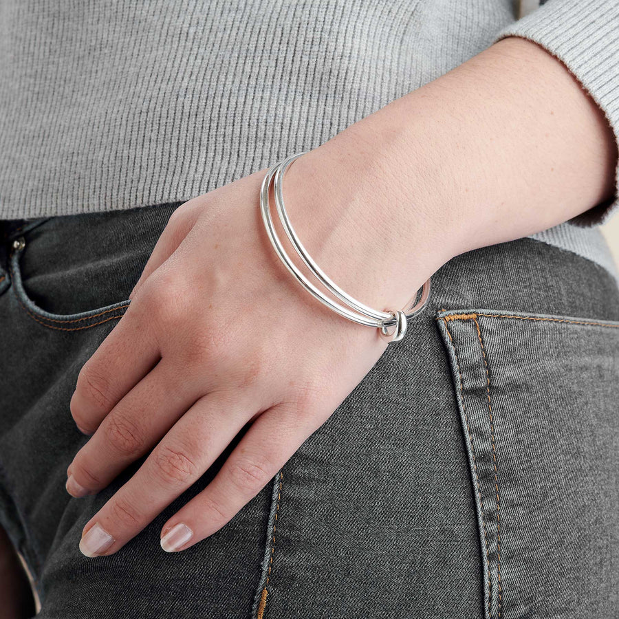 Two solid silver bangles joined in eternity by an asymmetrical Eclipse loop - a gorgeous designer made bangle for women.