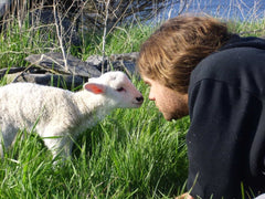 Young man with long brown hair lying in green grass, nose to nose with a small white lamb