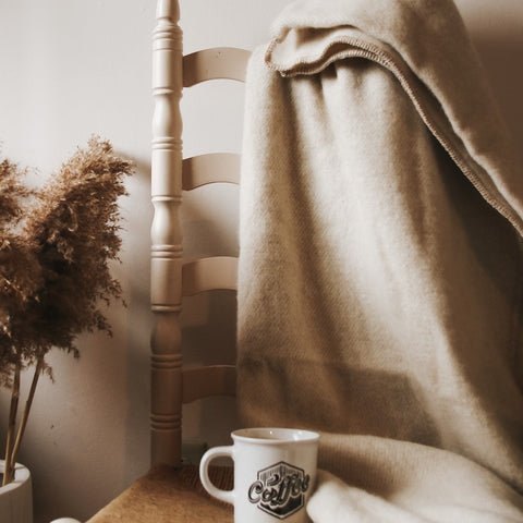Topsy Farms' champagne coloured alpaca wool blanket, draped over a wooden chair with a coffee cup on the seat