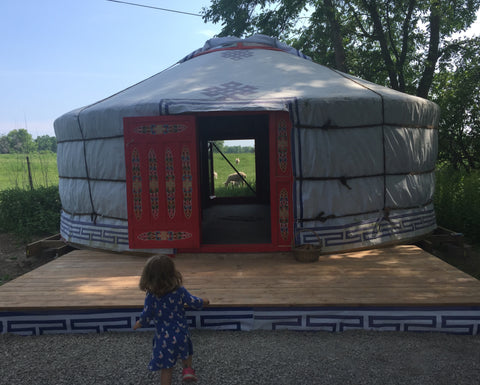 Traditional yurt with beautifully painted doors and a wooden deck, with a toddler in front and trees, and a field with sheep in the background