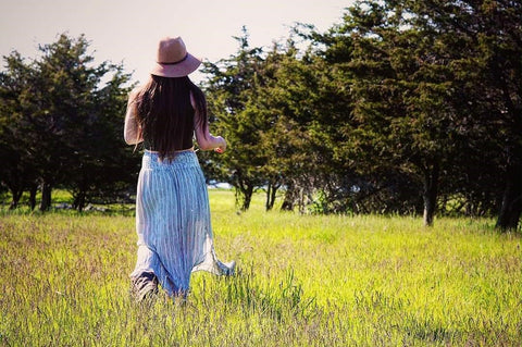Woman with long brown hair wearing a large felt hat and a long blue skirt, walking through a green field with conifers in the background, at Topsy Farms