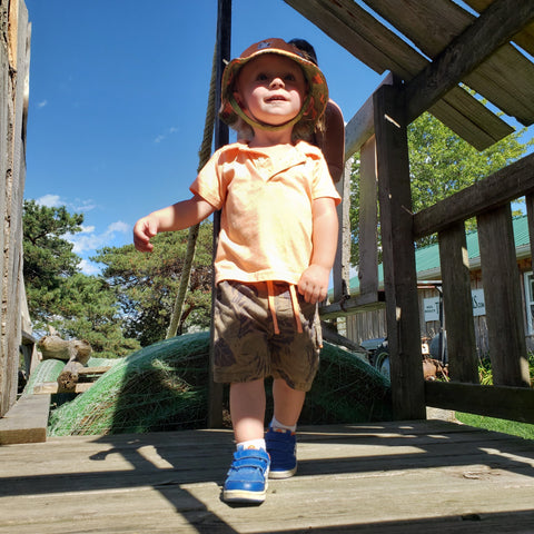 Young boy in yellow shirt, sun hat, and blue sneakers, standing on a wooden play structure smiling