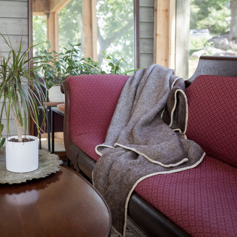 Topsy Farms' chestnut coloured Live Edge collection alpaca/wool blanket on an antique burgundy couch, in a sunroom, next to a wooden table with potted plants