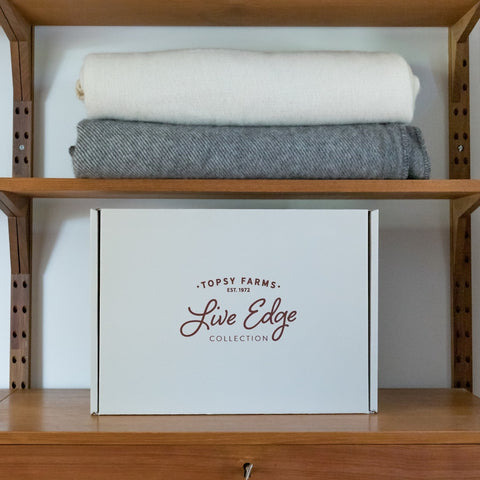 Topsy Farms' Live Edge collection alpaca/wool blend blankets in white and grey, folded on a brown wooden shelf, with a Live Edge box on the other shelf
