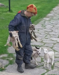 Woman wearing dark coveralls and a knitted hat on stone walkway, carrying 2 lambs with more at her feet