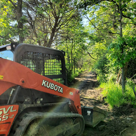 Kubota skid steer parked on a walking path through the forest at Topsy Farms