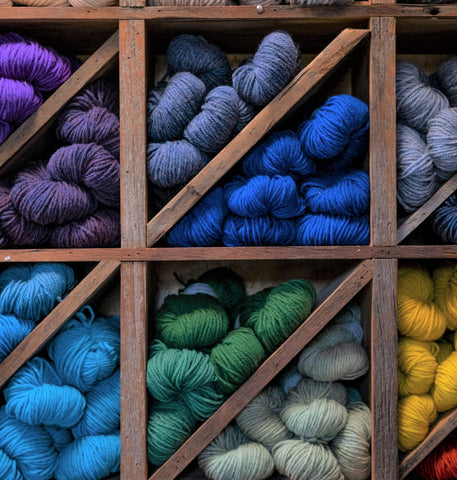 Close up of blue, green, yellow, and purple Topsy Farms' yarn on wooden shelving