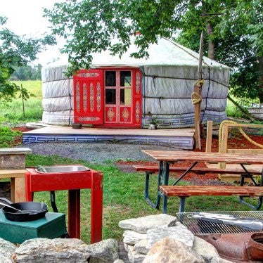 Traditional yurt with brightly painted doors, under trees on a green lawn with a picnic table and outdoor kitchen are in foreground