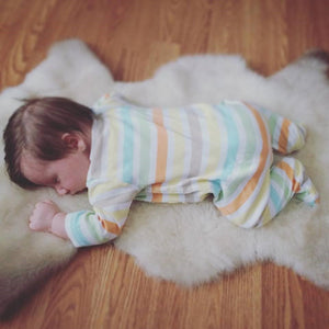 Dark-haired baby in striped onsie, sleeping face down on a white lambskin