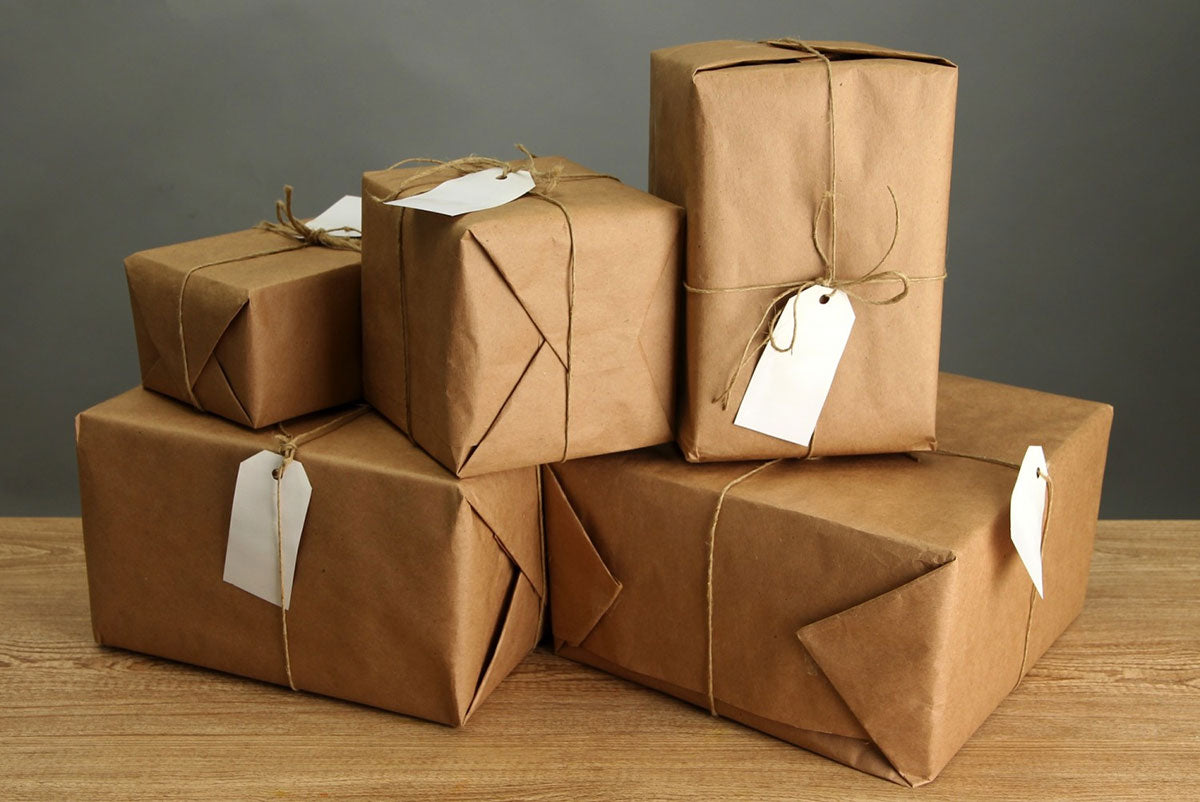 stack of boxes wrapped in craft paper, with shipping labels