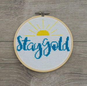 "Topsy Farms' cross stick with yellow sunburst and ""Stay Gold"" in blue script"
