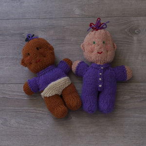 Knitted wool babies, one dark and one light skinned, on a grey barn board background