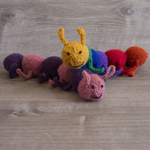 two knitted wool caterpillars, one rainbow coloured, one pink and purple, sitting on grey barn board