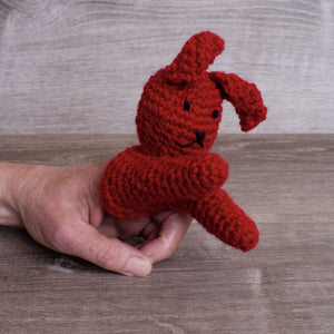 Red knitted wool bunny finger puppet on a white hand