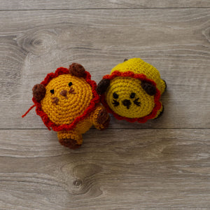 Two handmade wool lions, one yellow, one orange, on a grey barn board background