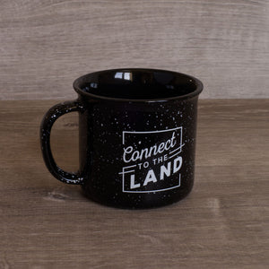 specked black and white ceramic mug, with white Connect to the Land logo