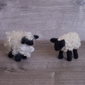 two small felted sheep, both white with black legs and face