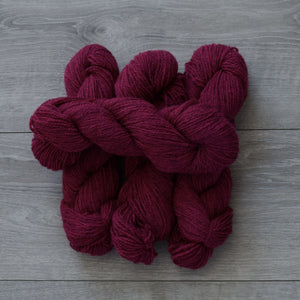 4 skeins of raspberry coloured Topsy Farms yarn on grey barnboard