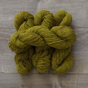 4 skeins of pear green Topsy Farms yarn on grey barnboard