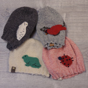Set of 4 knitted toques, with felted applique animals attached. Made with Topsy Farms' wool.