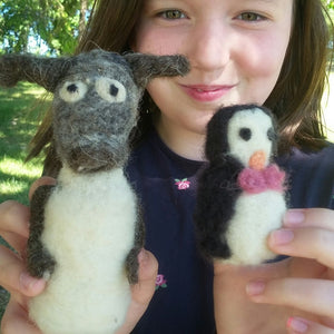 White girl with long dark hair, smiling and holding up a handcrafted wool penguin and dog